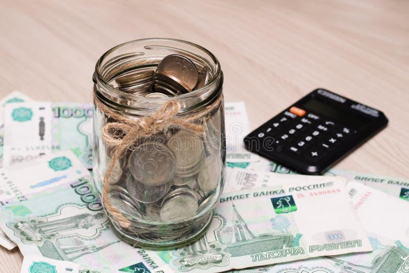 Pièces de monnaie en métal dans un pot en verre sur un fond des dénominations de papier de mille roubles sur la table près du cla photo stock