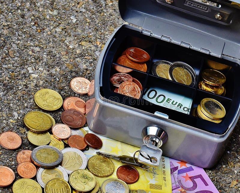 Pièces de monnaie et billets de banque dans la boîte en métal