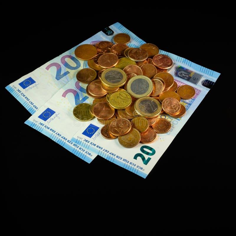 pièces de monnaie et billets de banque sur un fond noir photo libre de droits
