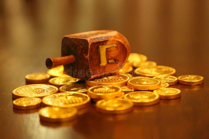 Pièces de monnaie de gelt d'or de dreidel de Hanoucca sur une table photographie stock