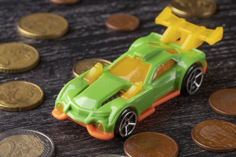 Pièces de monnaie de jouet et d'euro de voiture sur un fond en bois foncé images stock