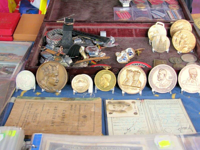 Pièces de monnaie, médailles et diplômes antiques à vendre sur un marché aux puces images stock