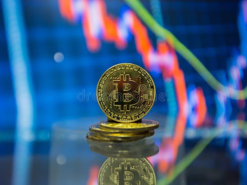 Pièces de monnaie physiques de Bitcoin en métal avec le diagramme d'échange commercial à l'arrière-plan photo libre de droits