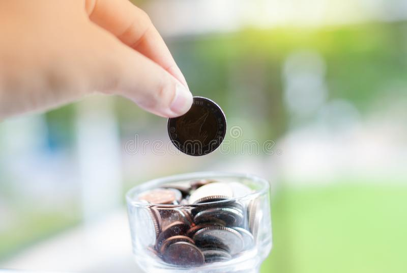 Pièces de monnaie qui se laissent tomber dans le pot - argent économisant images libres de droits