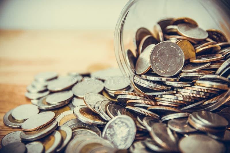 Pièces de monnaie se renversant hors d'une bouteille en verre images libres de droits