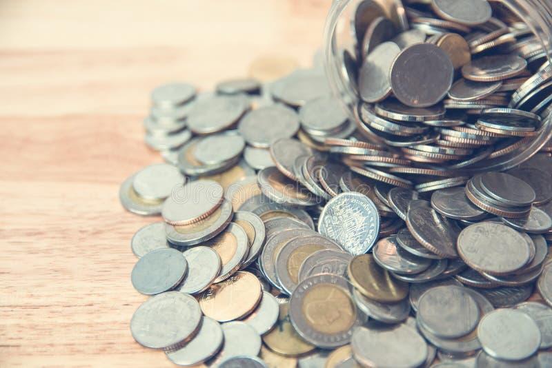 Pièces de monnaie se renversant hors d'une bouteille en verre photographie stock