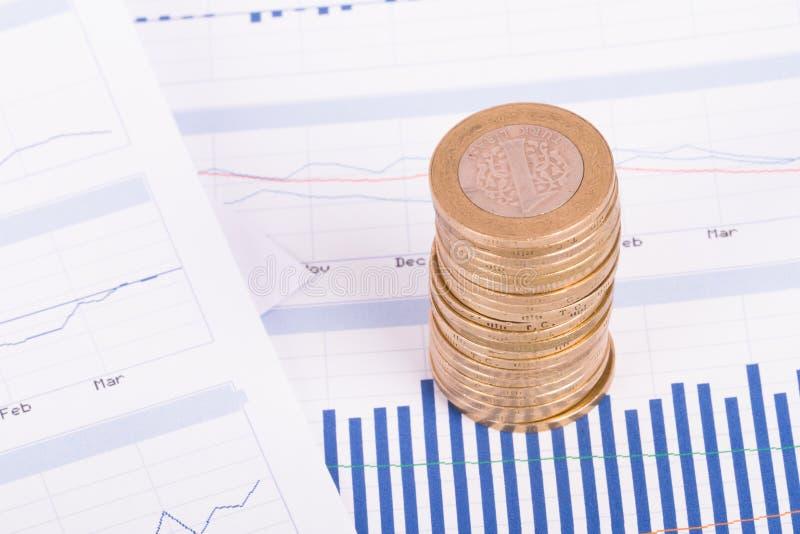 Pièces de monnaie sur des graphiques de diagramme et des données financières images stock