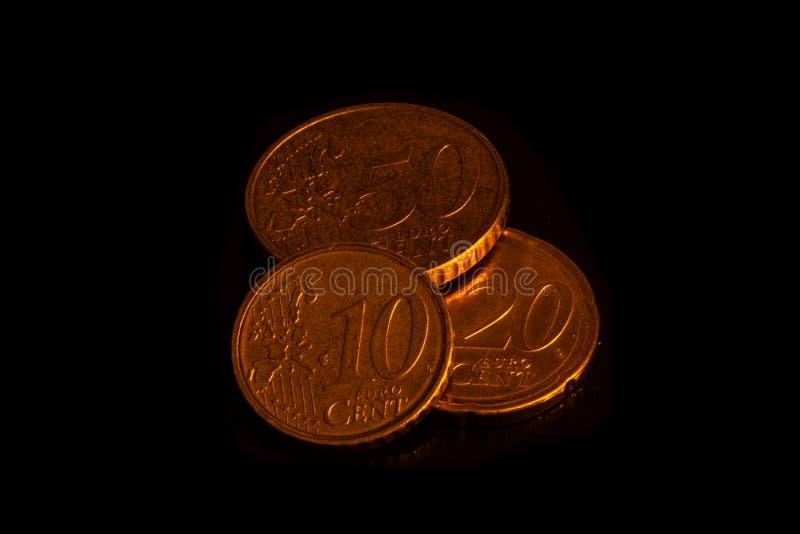 Pièces de monnaie sur le fond noir empilé image stock