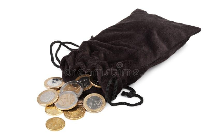 Pièces de monnaie tombant hors du sac d'isolement images stock