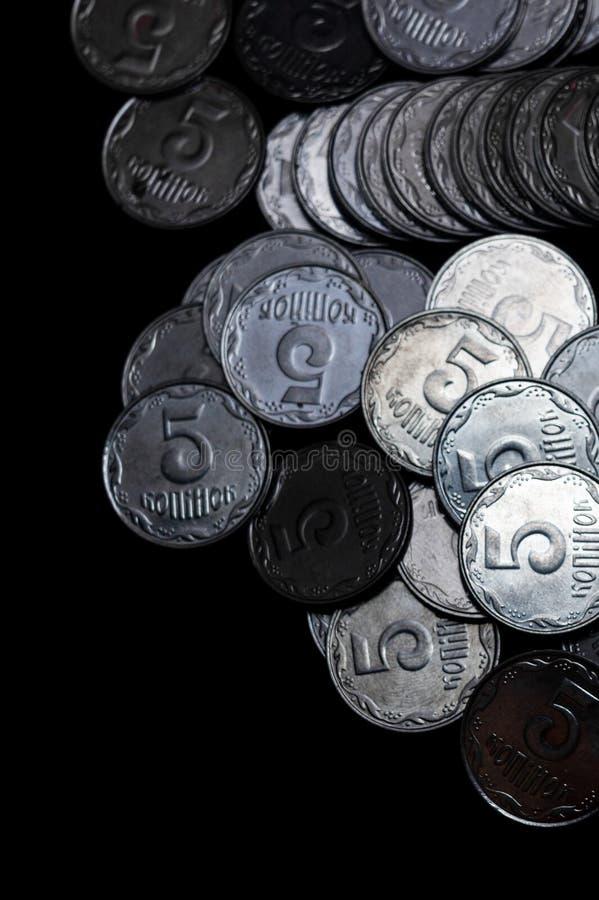 Pièces de monnaie ukrainiennes d'isolement sur le fond noir Vue de plan rapproché Des pièces de monnaie sont situées au-dessus du image stock