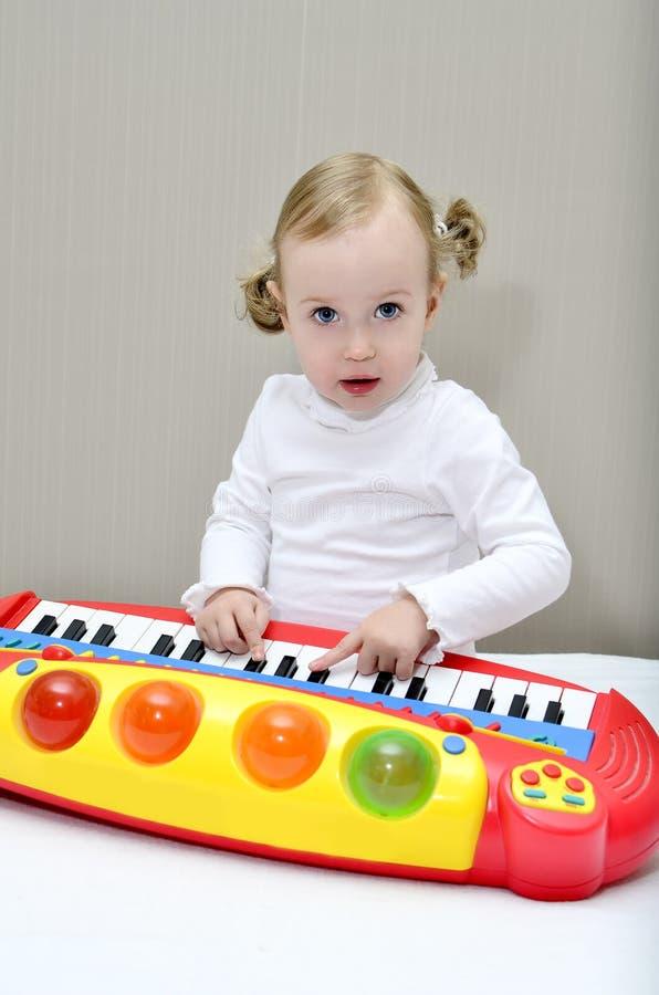 Pièces de petite fille sur un clavier d'enfants images stock
