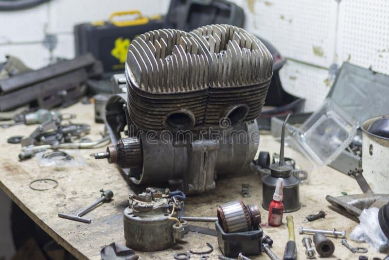 Pièces et outils de moto sur le bureau dans le garage images stock