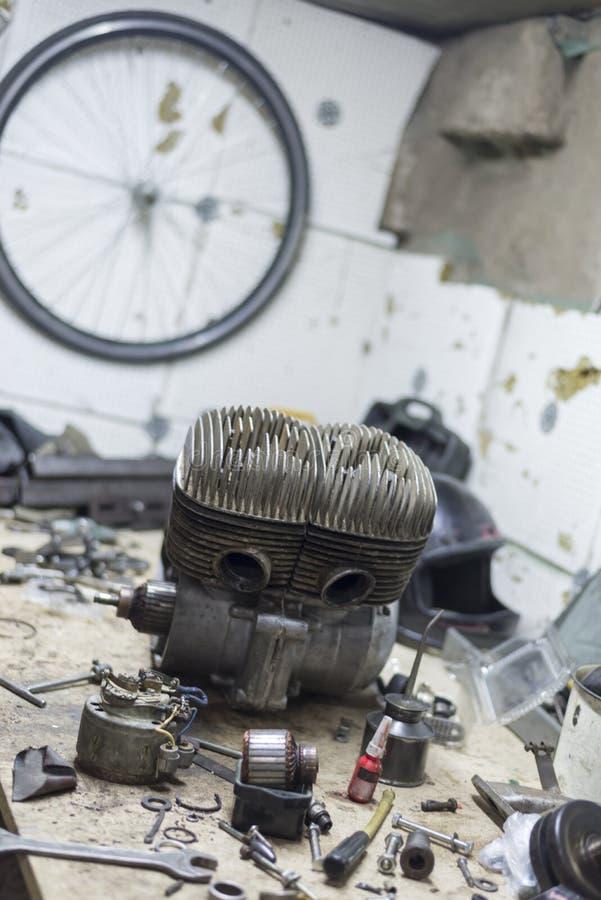 Pièces et outils de moto sur le bureau dans le garage photographie stock libre de droits