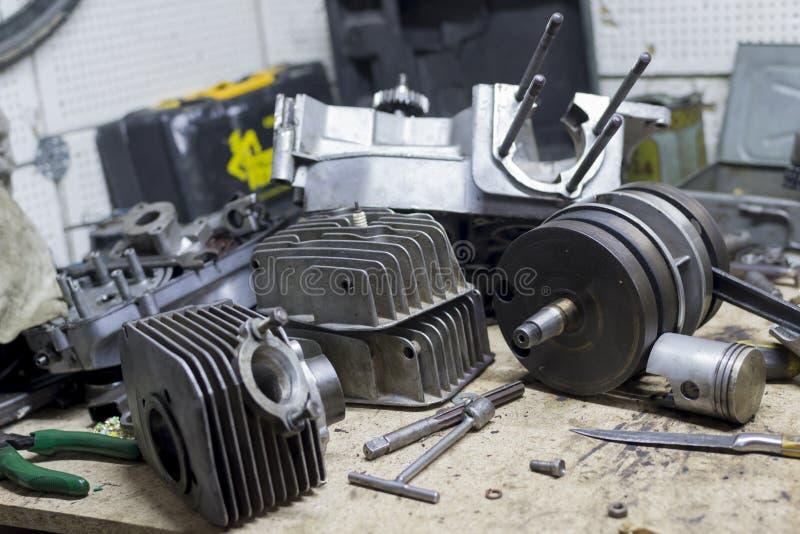 Pièces et outils de moto sur le bureau dans le garage photographie stock