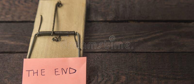 Piège de souris et le mot : L'EXTRÉMITÉ sur le fond en bois images libres de droits