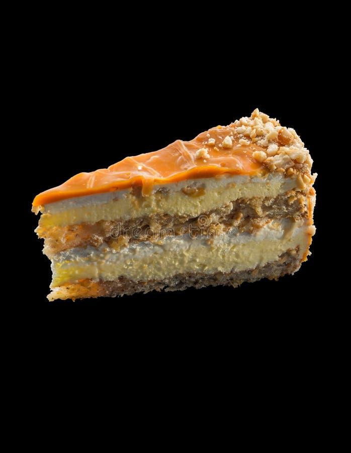 Piеce tort z karmelu glazerunkiem nad czarnym backgroun obraz royalty free
