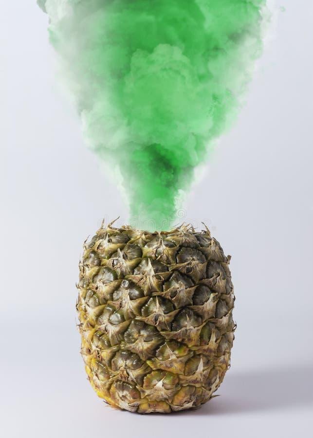 Piña con humo verde en el fondo blanco imagenes de archivo