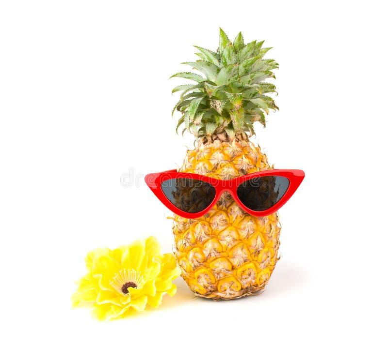 Piña fresca con gafas de sol rojas y flor aislada en fondo blanco imagen de archivo