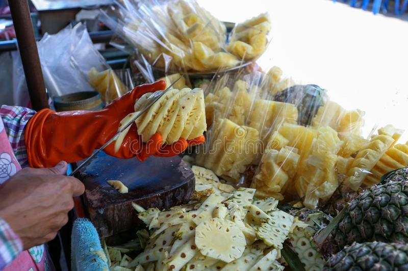 Piña local de la cáscara del vendedor en el mercado de Yaowarat, Bangkok, Tailandia foto de archivo