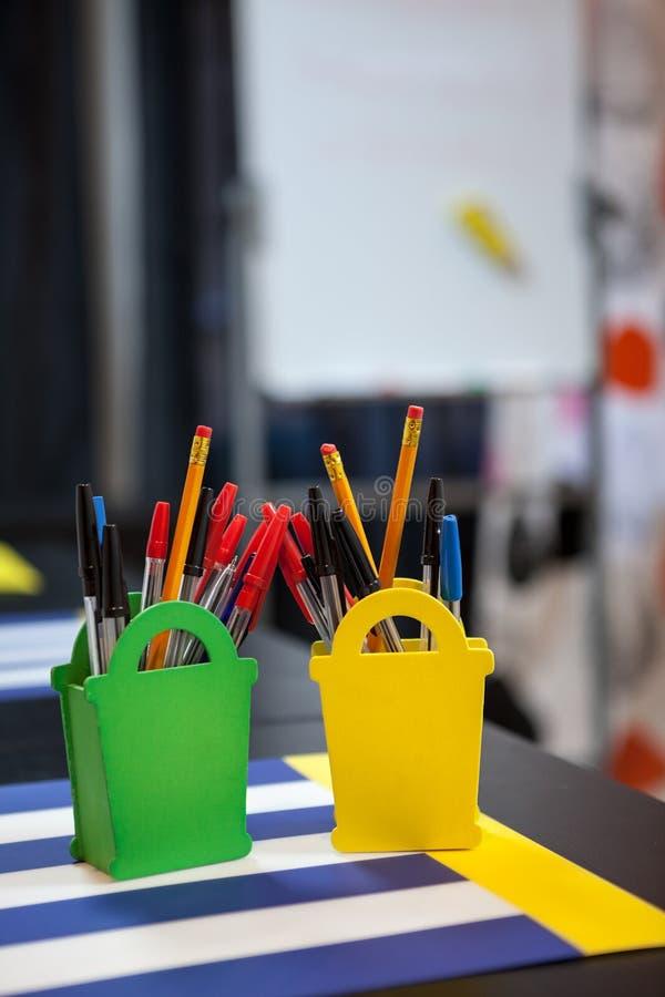Pióra i pensils są w organizatorze przy stołem zdjęcia stock