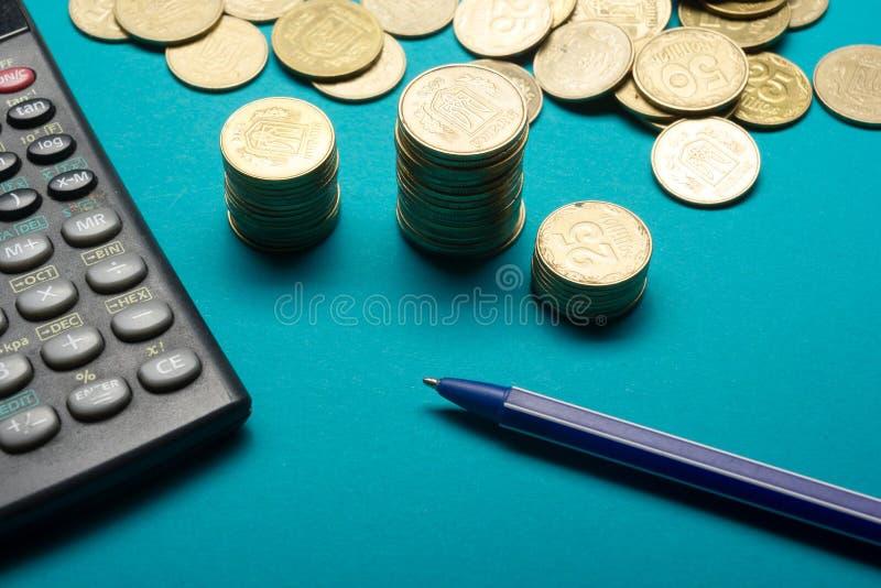 Pióra, pieniądze monet sterta, i kalkulator dla finansowego pojęcia zdjęcie royalty free