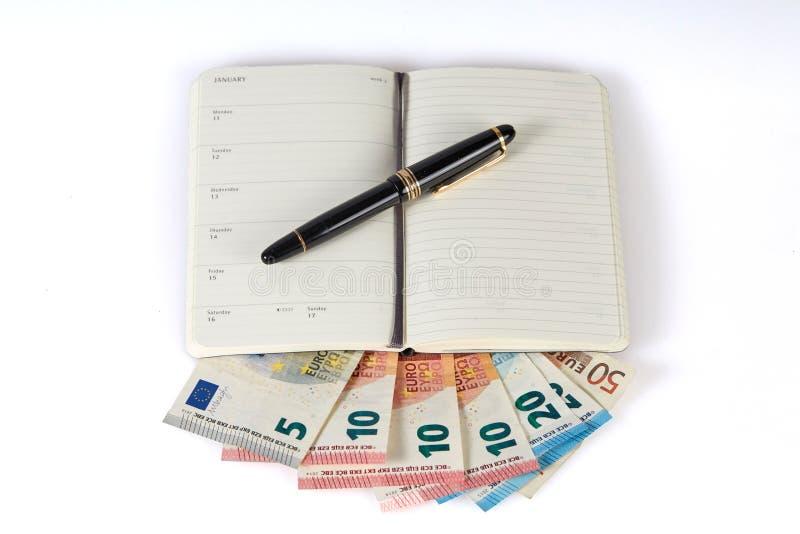 Pióro i książka odizolowywający na europejskich banknotach zdjęcie stock