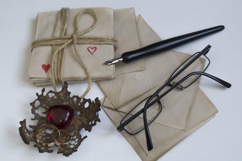Pióro i szkła jesteśmy na notatkach z sercami obraz stock