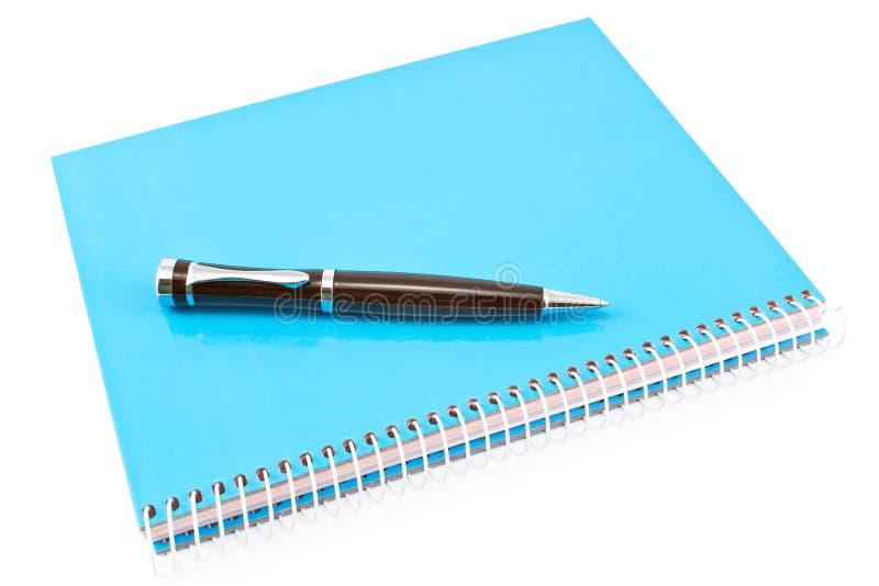 Pióro na błękitnym ślimakowatym notatniku obraz stock
