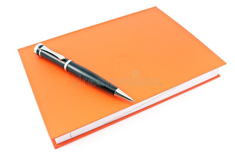 Pióro na czerwonym notatniku obrazy stock