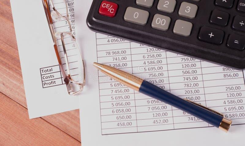 Pióro, szkła i kalkulator na papierowych stołach z liczbami, zdjęcie royalty free