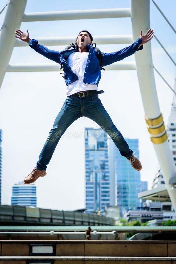 Più forte uomo asiatico che salta e che corre con la costruzione e il citysc immagine stock libera da diritti