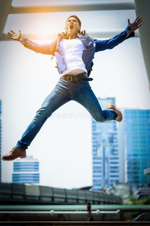 Più forte uomo asiatico che salta e che corre con la costruzione e il citysc immagini stock libere da diritti