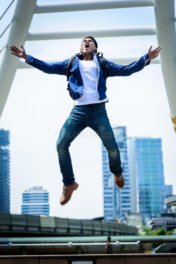 Più forte uomo asiatico che salta e che corre con la costruzione e il citysc fotografia stock libera da diritti