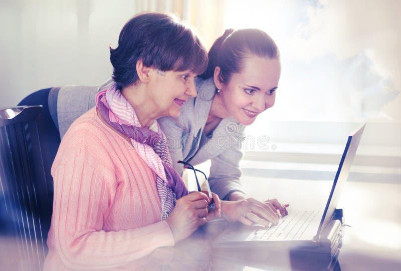 Più giovane donna che aiuta una persona anziana che per mezzo del computer portatile fotografia stock libera da diritti