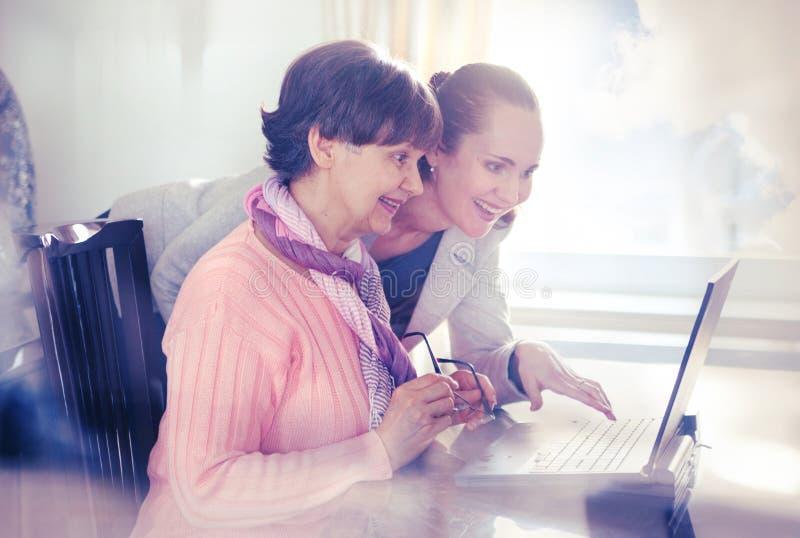 Più giovane donna che aiuta una persona anziana che per mezzo del computer portatile fotografia stock