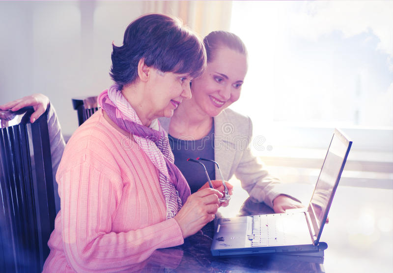 Più giovane donna che aiuta una persona anziana che per mezzo del computer portatile per la ricerca di Internet fotografia stock