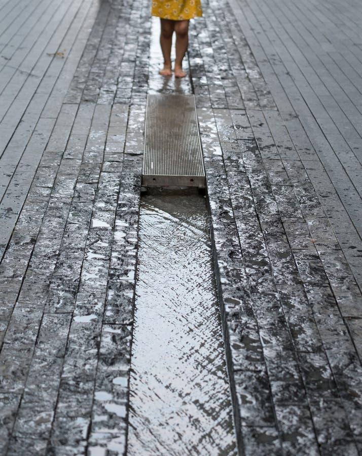 Più Londra sulla sponda sud del Tamigi La foto mostra le gambe del bambino che giocano nel waterin un canale nella via fotografia stock libera da diritti