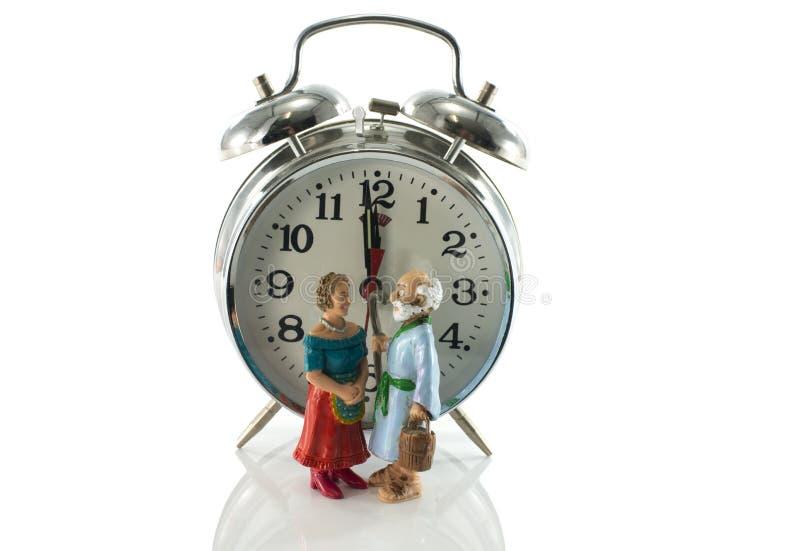 Più vecchie coppie che aspettano all'orologio immagini stock