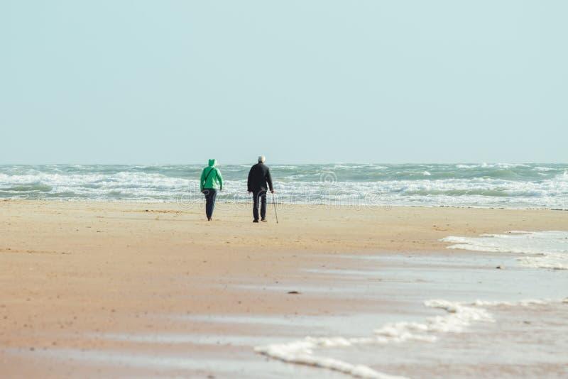 Più vecchie coppie che camminano alla spiaggia immagine stock