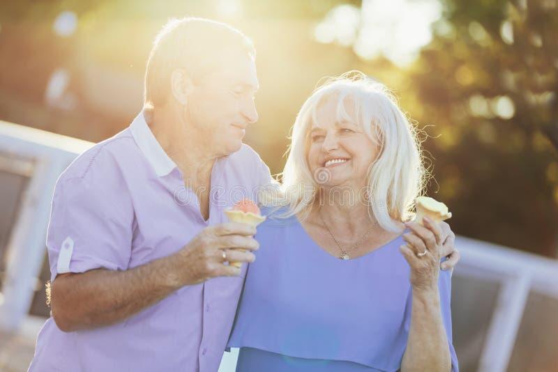 Più vecchie coppie che mangiano il gelato e camminata immagine stock libera da diritti