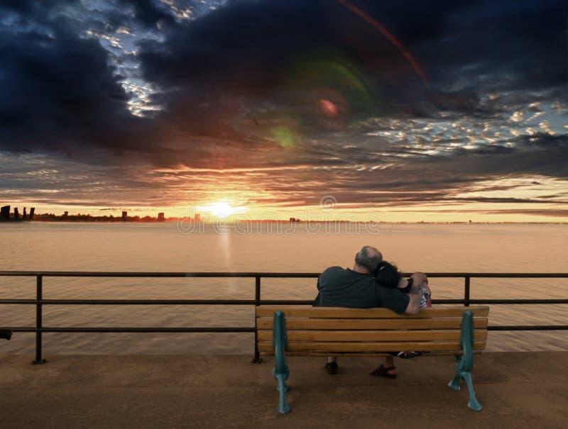 Più vecchie coppie sul banco che gode del tramonto immagini stock