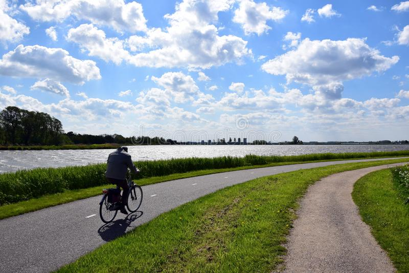Più vecchio ciclismo del motociclista contro il vento di prua del te nel paesaggio olandese fotografie stock libere da diritti