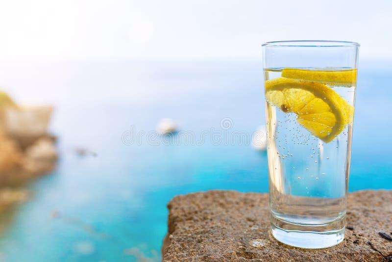 Pić szkło z zimno carbonated napoju, cytryny plasterkiem przeciw wodnego lub miękkiego i obraz stock