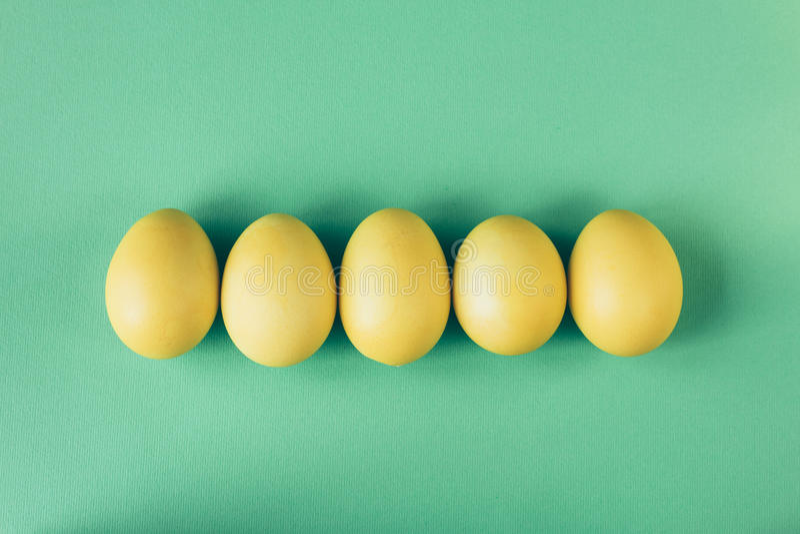 Pięć żółtych jajek kłamają na zielonego tła odgórnym widoku zdjęcia stock