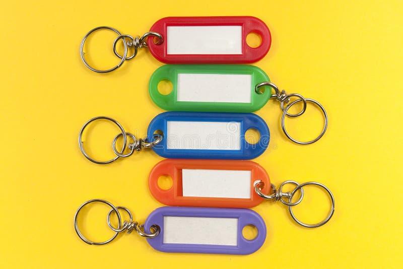 Pięć barwiący kluczowy właściciel z białą etykietką na żółtym tle zdjęcia royalty free