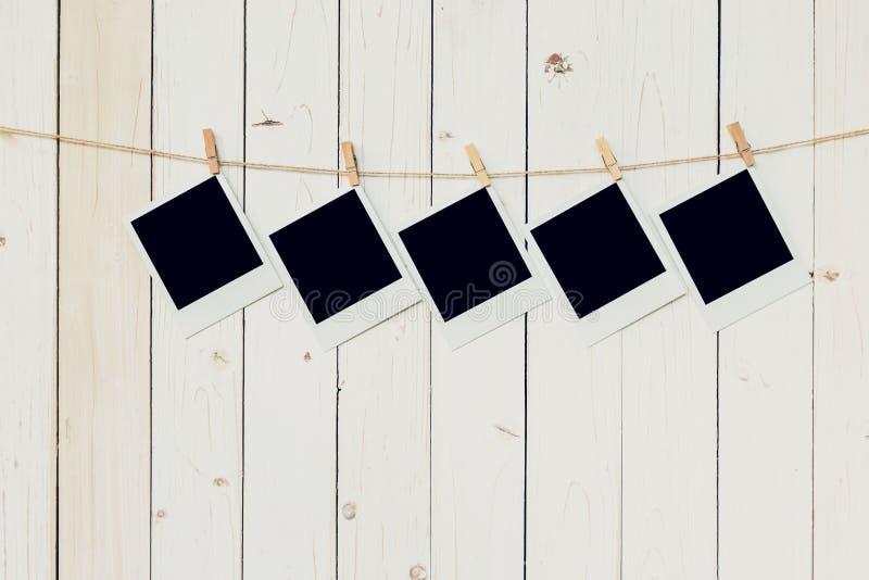 Pięć 5blank fotografii ramy obwieszenie na białym drewnianym tle z fotografia stock