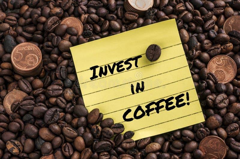Pięć centów euro moneta nad świeżą kawą piec fasole i notatkę z zwrotem: inwestuje w kawie zdjęcie royalty free