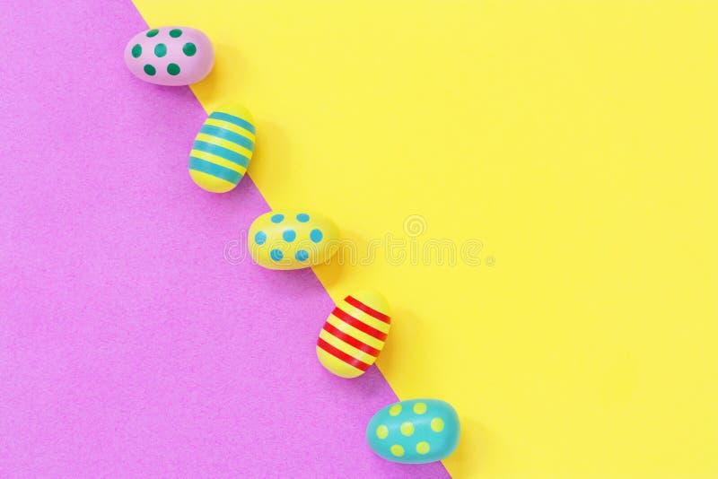 Pięć colourful Wielkanocnych jajek przeciw koloru żółtego i menchii przekątny tłu obraz stock