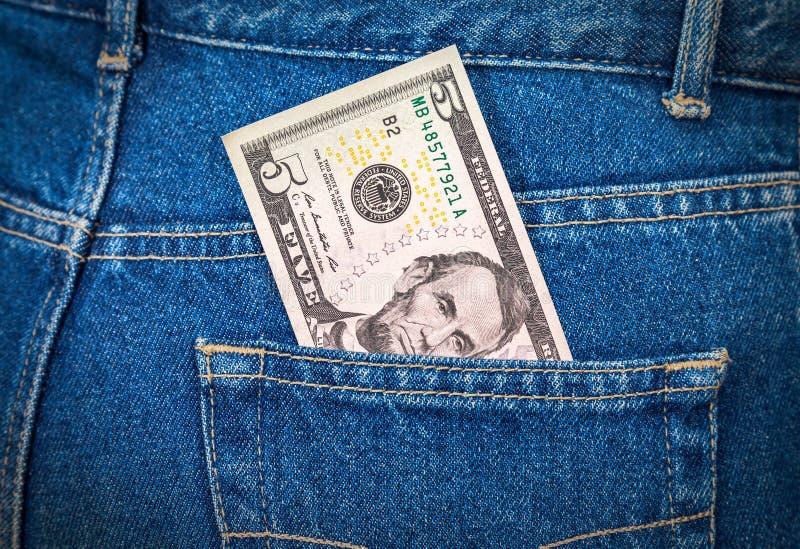 Pięć dolarów rachunku klejenia z cajg kieszeni obraz stock