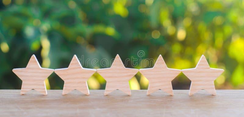 Pięć drewnianych gwiazd Dostaje kwinty gwiazdę Pojęcie ocena cenienie krytycy, goście, i obrazy royalty free